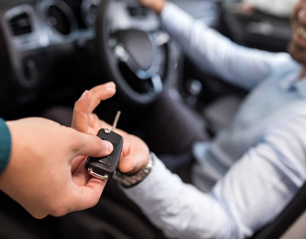 Close up of a man sitting in a car and receiving car keys from unrecognizable person.