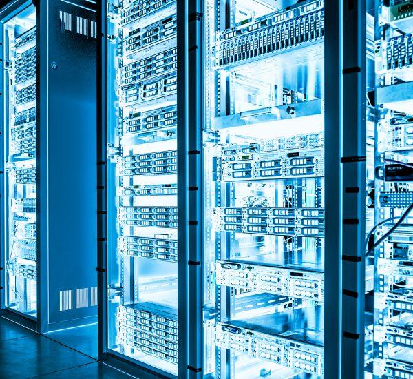 Servers in rows on metal shelves in dark cooling room