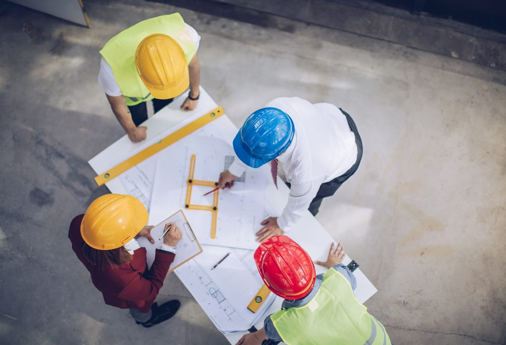 Construction workers and architects working on construction site