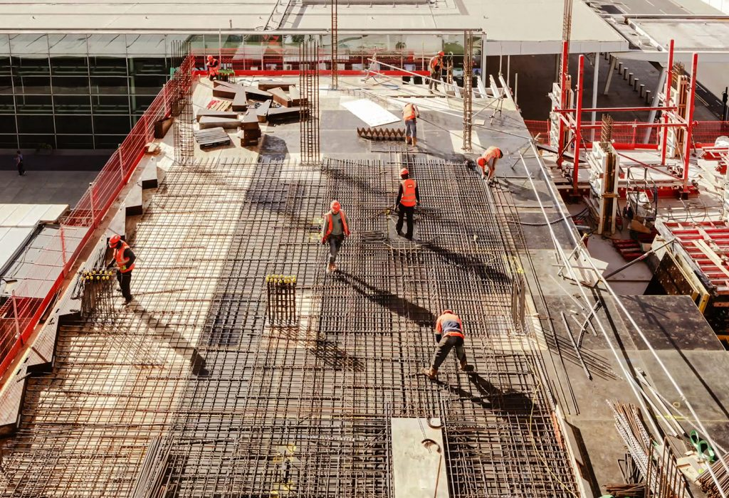 Construction workers at a construction site viewed from above, High angle view of five people with helmets.