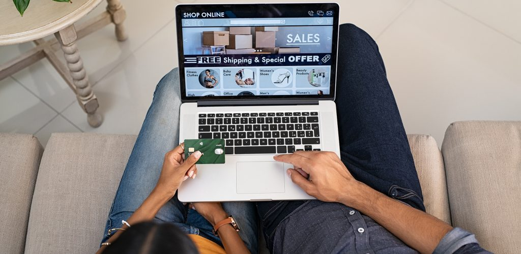 Top view of indian couple doing shopping online on website with laptop at home. High angle view of man and woman using laptop on legs and paying with credit card. Indian casual couple selecting product on ecommerce portal on computer.